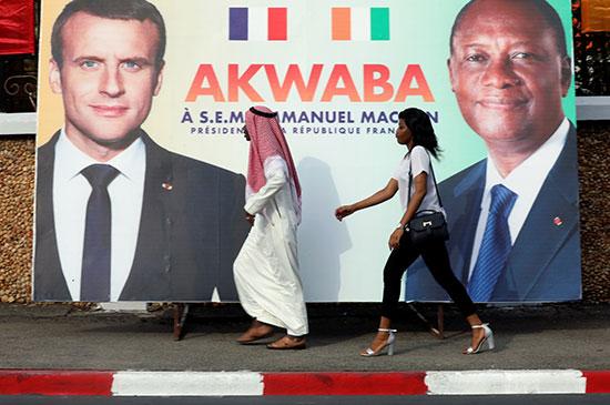 المارة عبر لافتة للرئيس الفرنسي إيمانويل ماكرون ونظيره في ساحل العاج الحسن واتارا