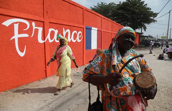 نساء يمشون وراء حائط ملون قبل وصول الرئيس الفرنسي إلى ساحل العاج
