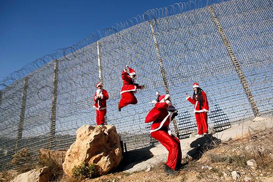 أطفال فلسطينيون يرتدون ملابس بابا نويل يقفزون بالقرب من الجدار الإسرائيلى