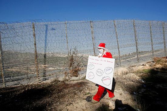 متظاهر فلسطينى يرتدى زى بابا نويل بالقرب من الجدار الإسرائيلى فى الضفة الغربية
