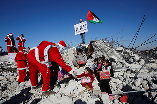 متظاهر يرتدى زى بابا نويل يوزع هدايا على الأطفال الجالسين فوق أنقاض منزل