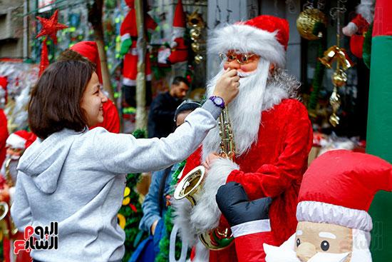 فتاة تداعب بابا نويل