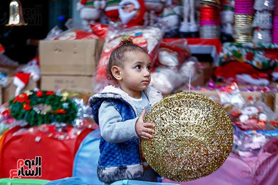 طفلة تختار زينة الكريسماس