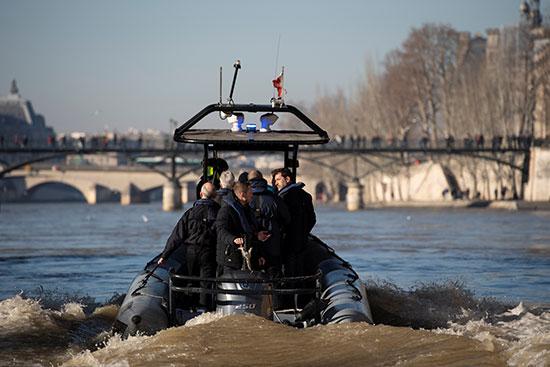 كريستوف كاستانير يقف على متن قارب شرطة