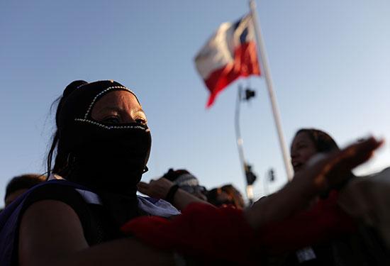 امرأة ترتدي قناعًا تشارك في احتجاج معارض للعنف ضد المرأة