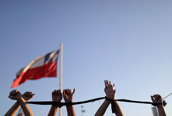 متظاهرات ترفعن أيديهم كنوع من الاحتجاج على العنف ضد المرأة