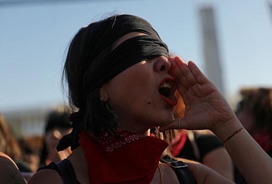 امرأة ترتدى عصابة سوداء تهتف فى مظاهرة نسائية مناهضة للعنف ضد المرأة