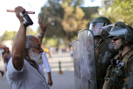 مواطن تشيلى يقف أمام قوات الأمن