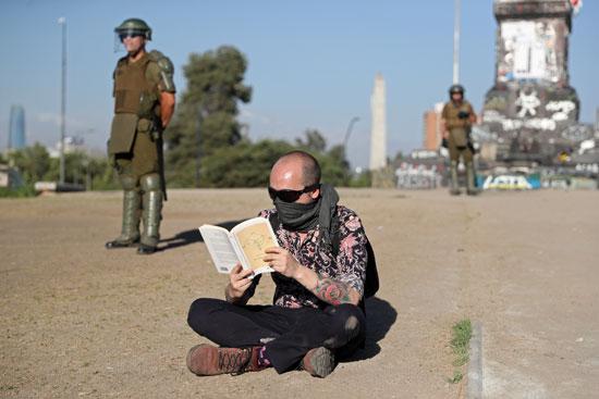 الاحتجاج بالقراءة.. متظاهر يقرأ كتاب أمام قوات الأمن