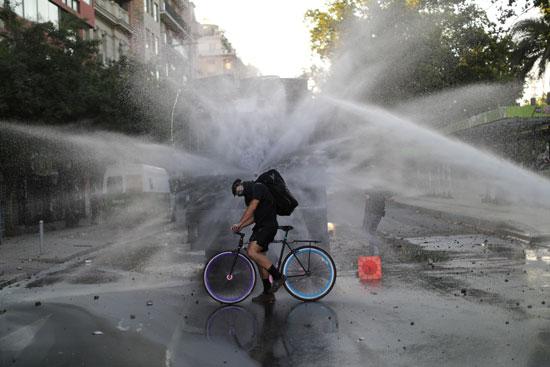 متظاهر يقود دراجته محاصر برشاشات المياه التى أطلقتها الشرطة