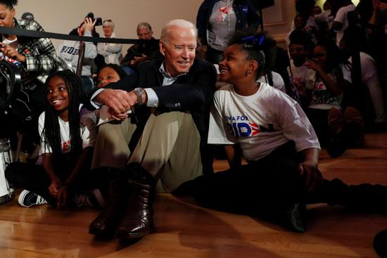 جو بايدن يجلس على الأرض بجوار طفلة من أصل أفريقى