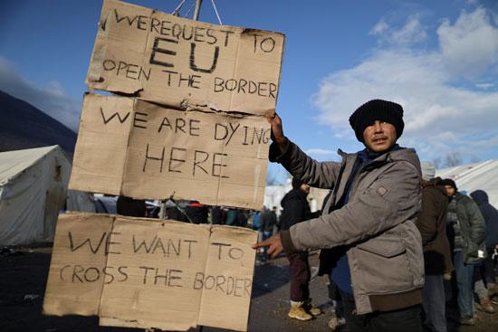 لافتة يرفعها أحد المهاجرين