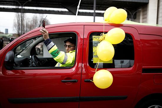 متظاهر يمر بسيارته وسط الاحتجاجات ويرفع بعض البالونات