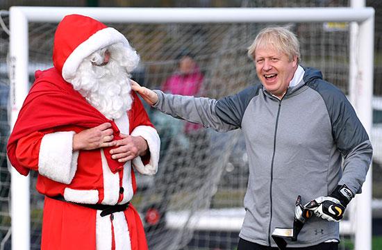 جونسون يحيي رجلاً يرتدي زي بابا نويل أثناء عملية الاحماء قبل مباراة كرة القدم البناتية