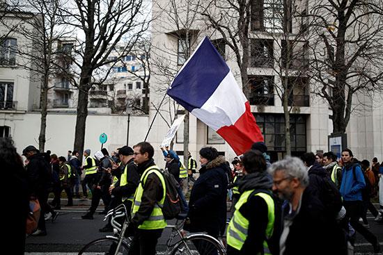 مرتدو السترات الصفراء يرفعون العلم الفرنسى خلال احتجاجاتهم