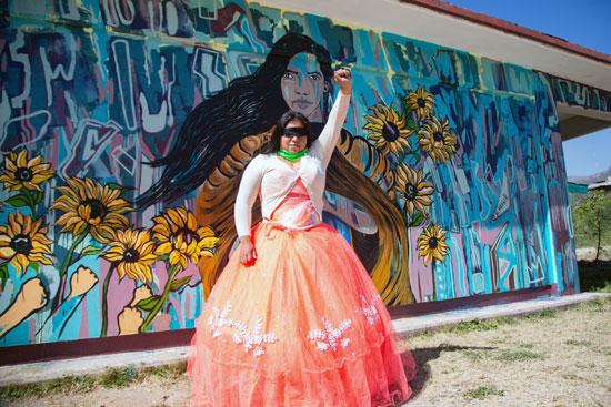 إحدى الطالبات تقوم بالتقاط صورة أمام الجرافيتى