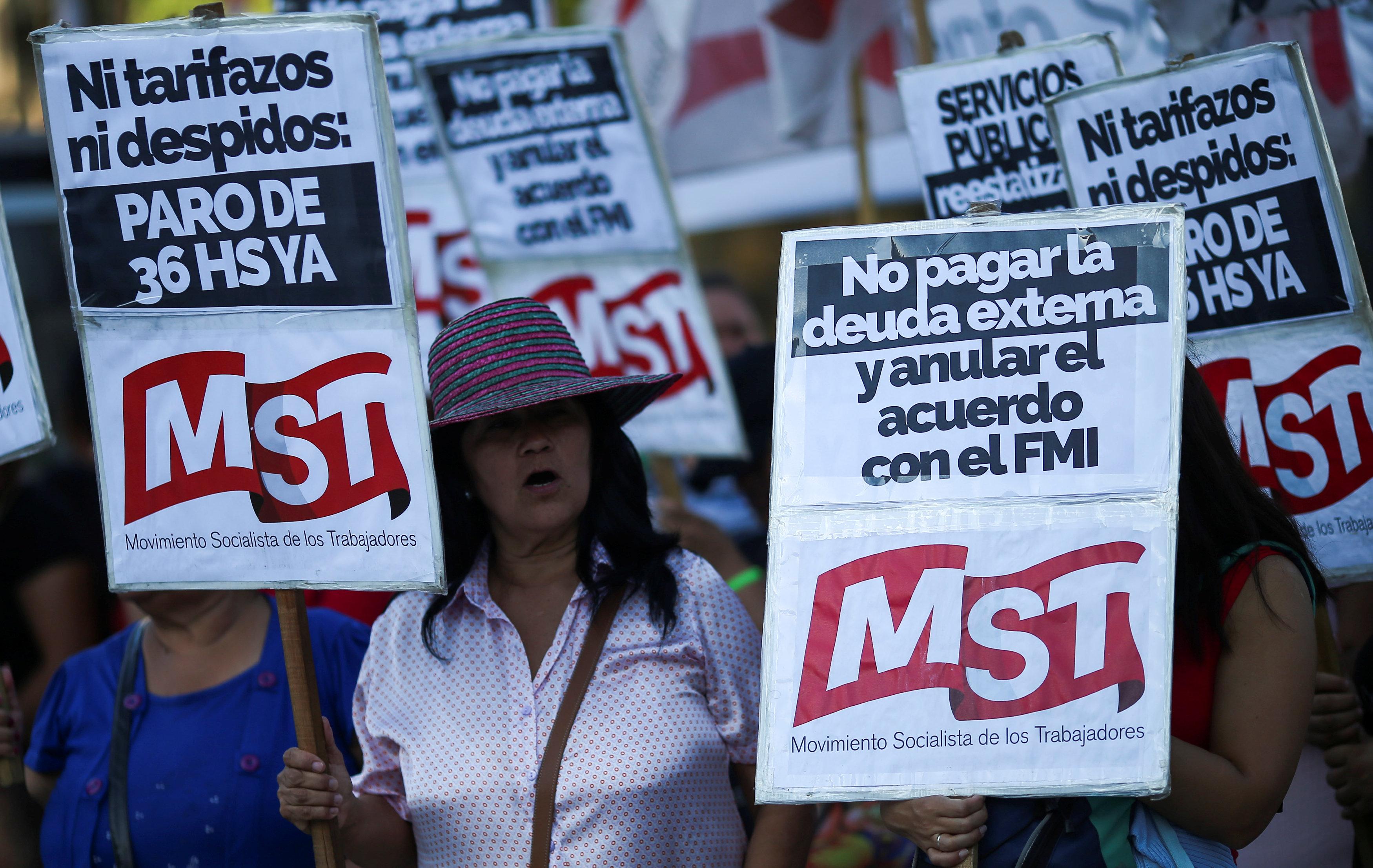 متظاهرون يرفعون اللافتات المناهضة للحكومة