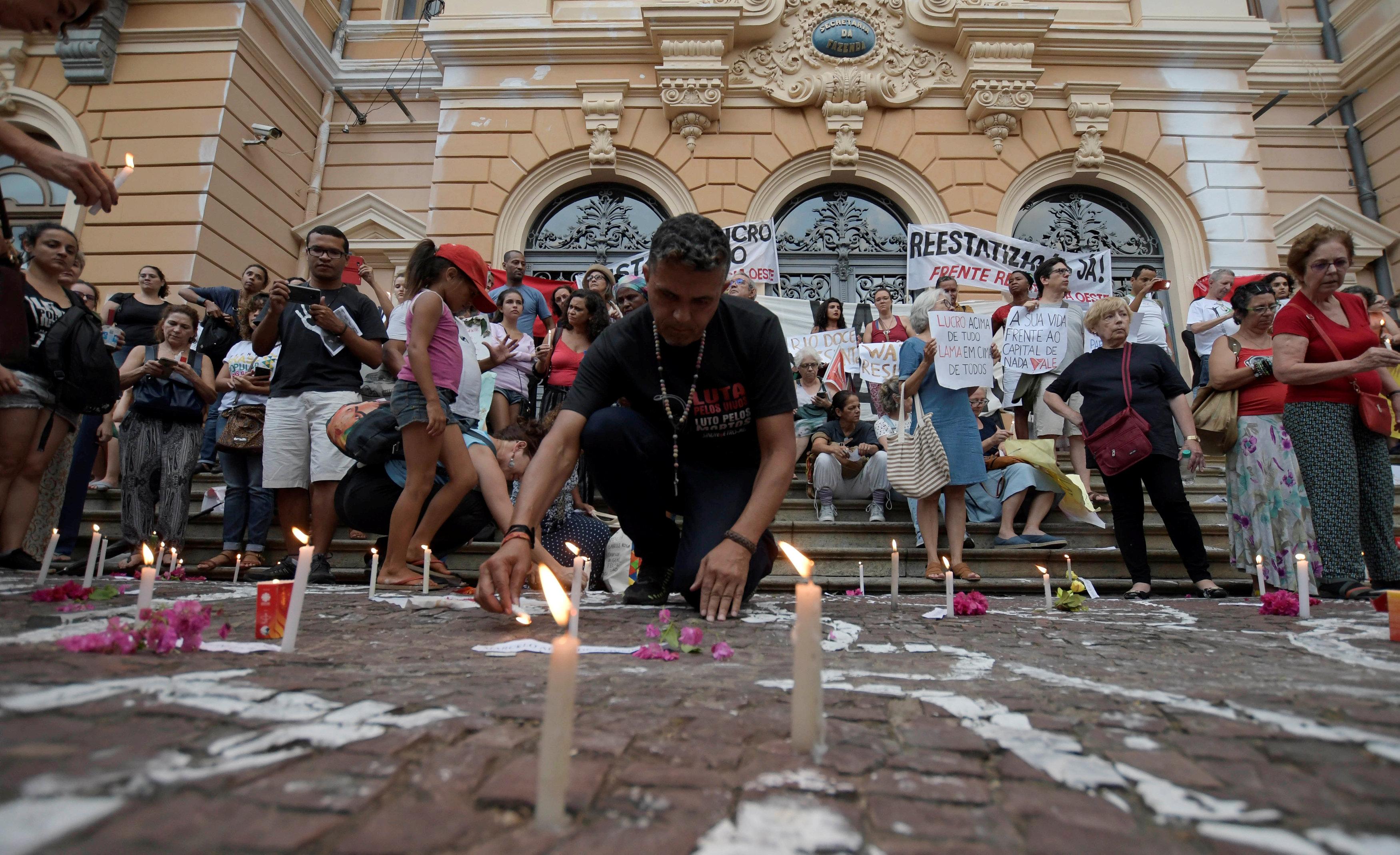 متظاهرون يحملون اللافتات ويضعون الشموع لتكريم الضحايا