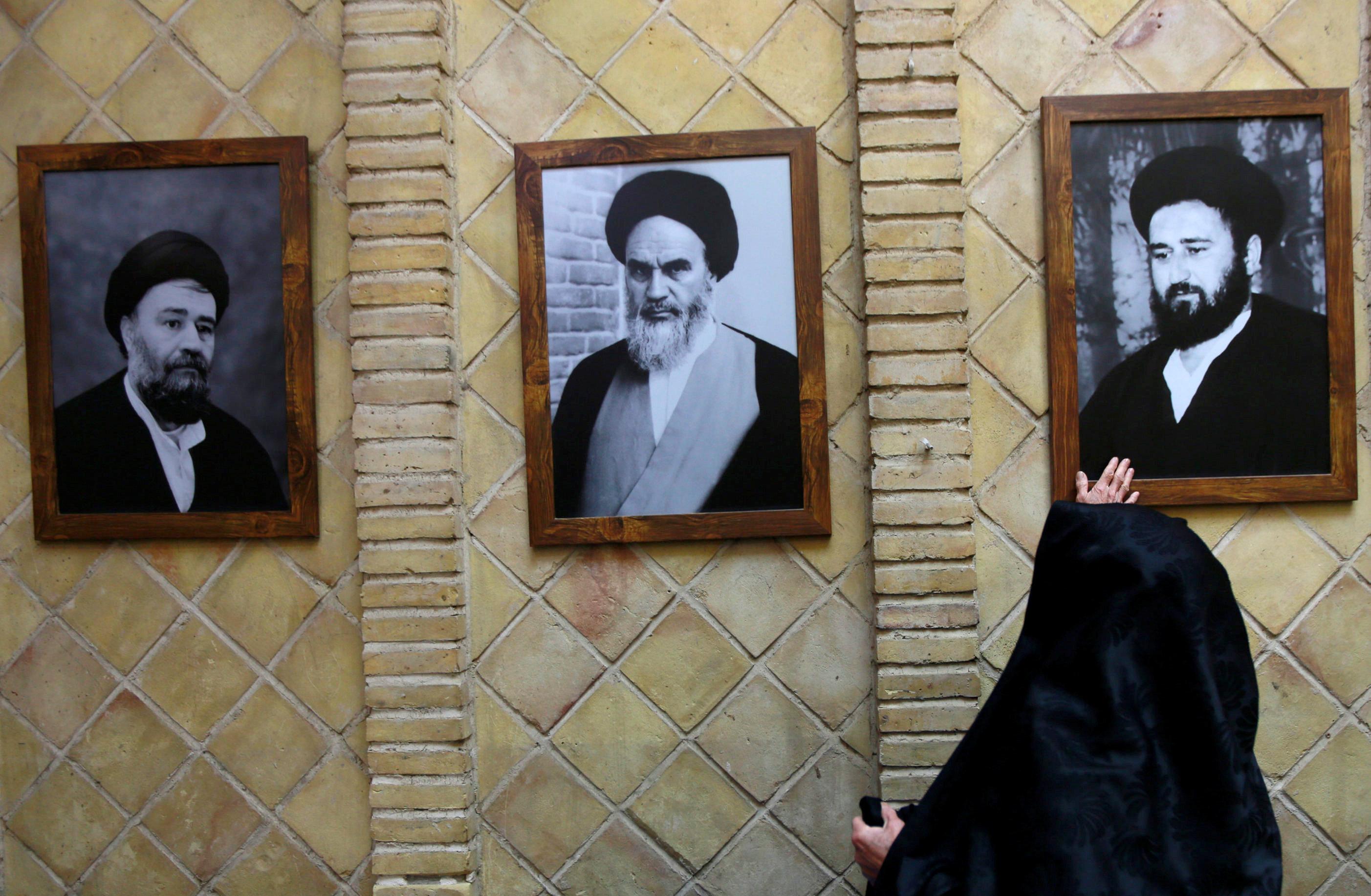 سيدة إيرانية تتبرك بصورة أحد مرشدى الثورة الإيرانية بمنزل الخمينى