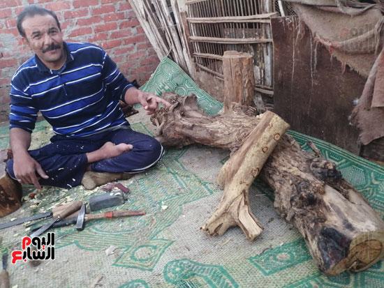 3328722-احمد-وبجواره-الاخشاب-التى-ينحت-منها-التماثيل