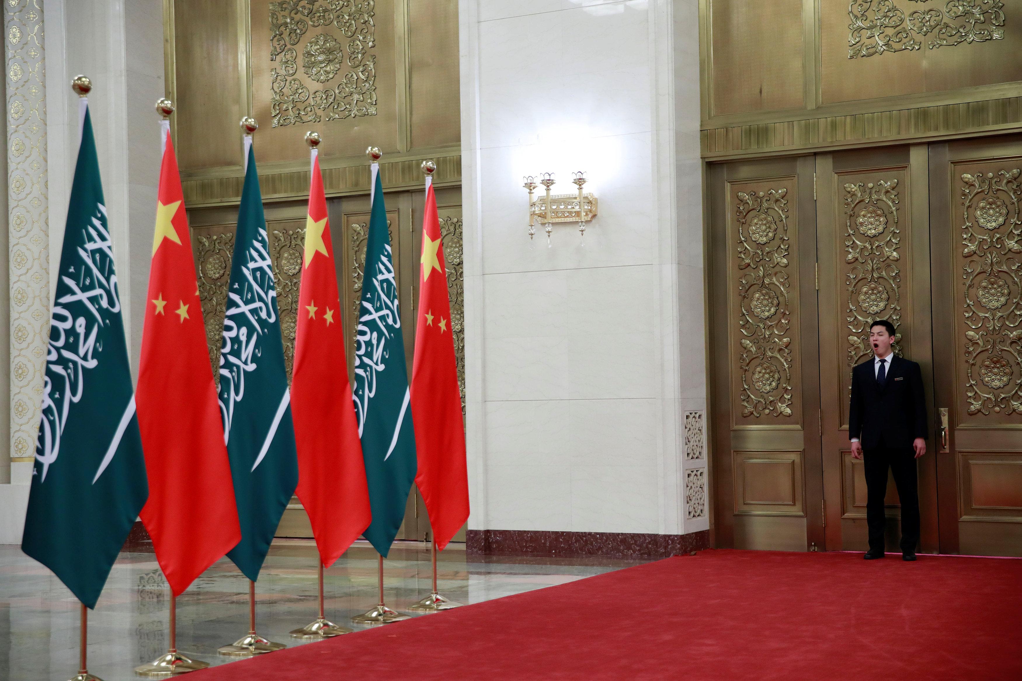 أعلام الصين والسعودية خارج غرفة الاجتماعات