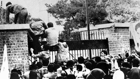 طلاب إيرانيون يتسلقون سور السفارة الأمريكية فى طهران 4 نوفمبر 1979 حيث احتجزوا 52 رهينة لمدة 444 يوما