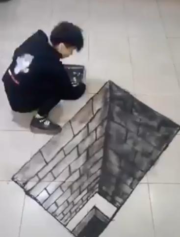 الشاب خلال إبداعه لأحد اللوحات ورسمها على الأرض