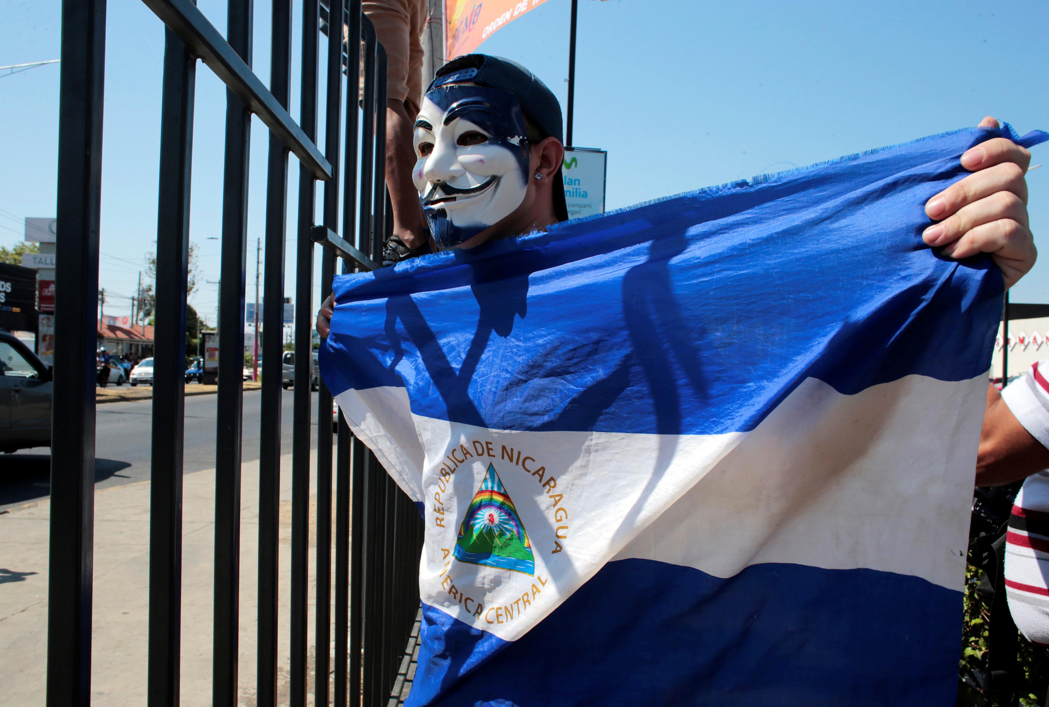أحد المتظاهرين يرفع علم البلاد