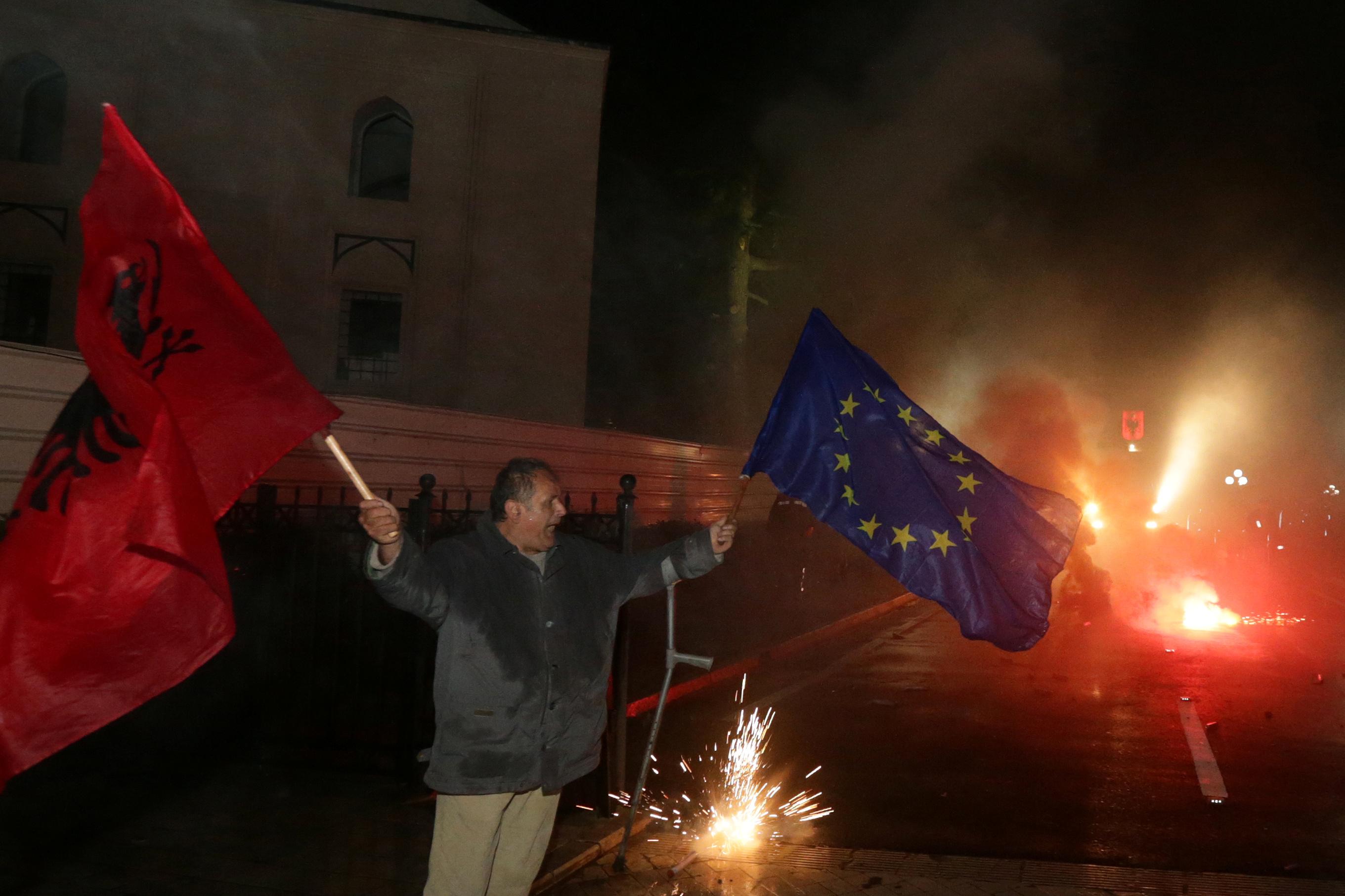 أحد أنصار حزب المعارضة يلوح بالعلم الألباني والأوروبي خلال مظاهرة مناهضة للحكومة أمام مبنى البرلمان في تيرانا