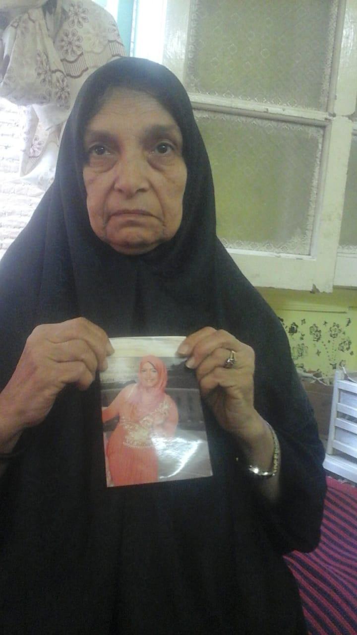 والدة الضحية تحمل صورتها