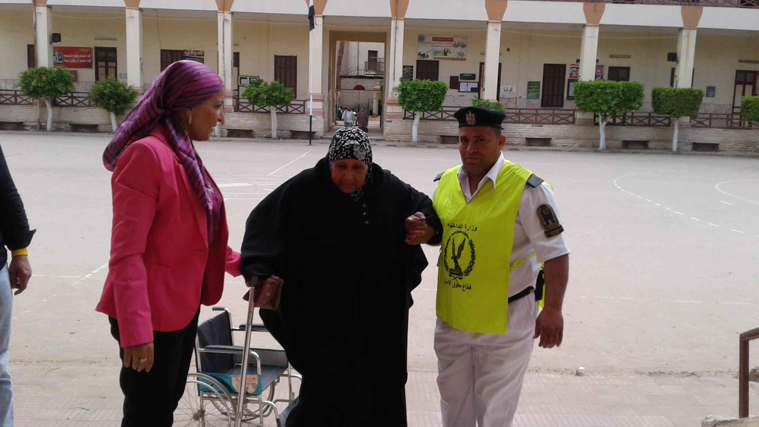 رئيسة اللجنة أثناء مساعدتها أحد المسنات للدخول للجنة (1)
