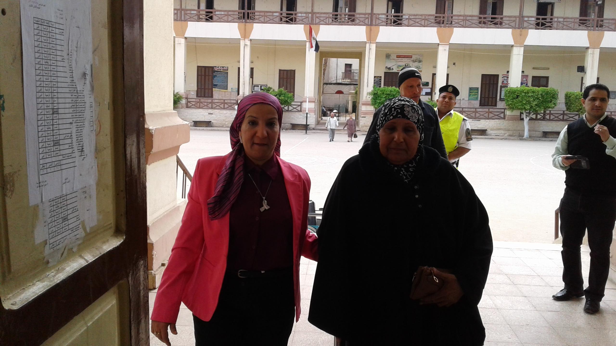 رئيسة اللجنة أثناء مساعدتها أحد المسنات للدخول للجنة (3)