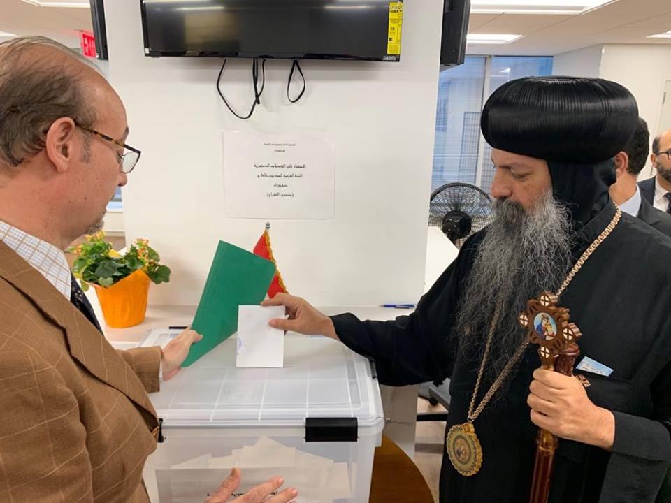 اسقف نيوريوك يضع ورقة التصويت بعد الانتهاء من المشاركة فى الاستفتاء