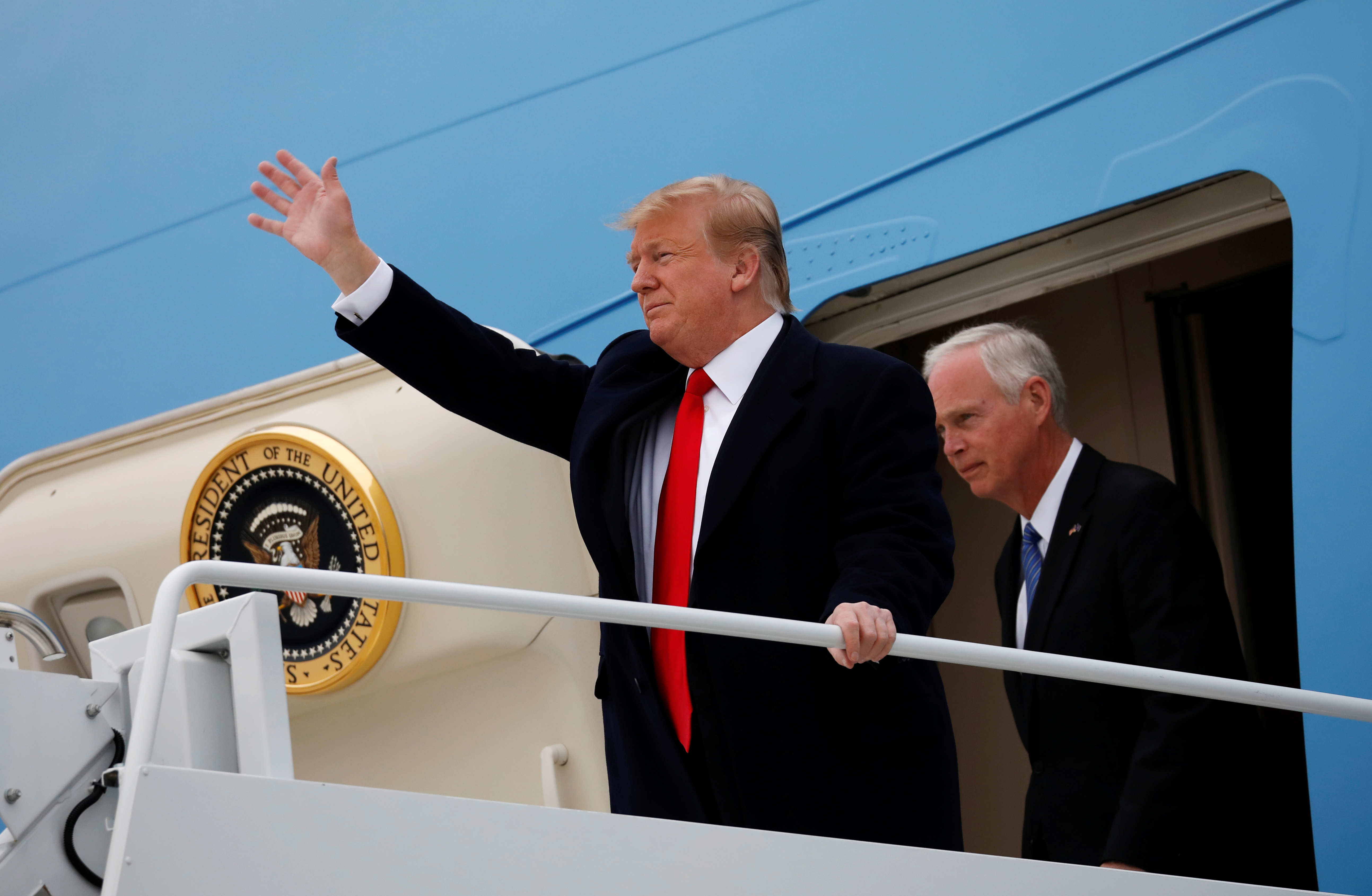 الرئيس الأمريكي دونالد ترامب يحيي الناس عند وصوله إلى مطار أوستن
