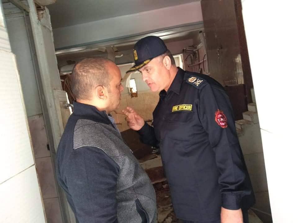 رجل الاطفاء يستعلم عن العقار المنهار من احد السكان