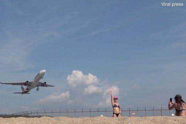 السياح يلتقطون الصور مع صعود الطائرات من المطار القريب من الشاطئ فى تايلاند