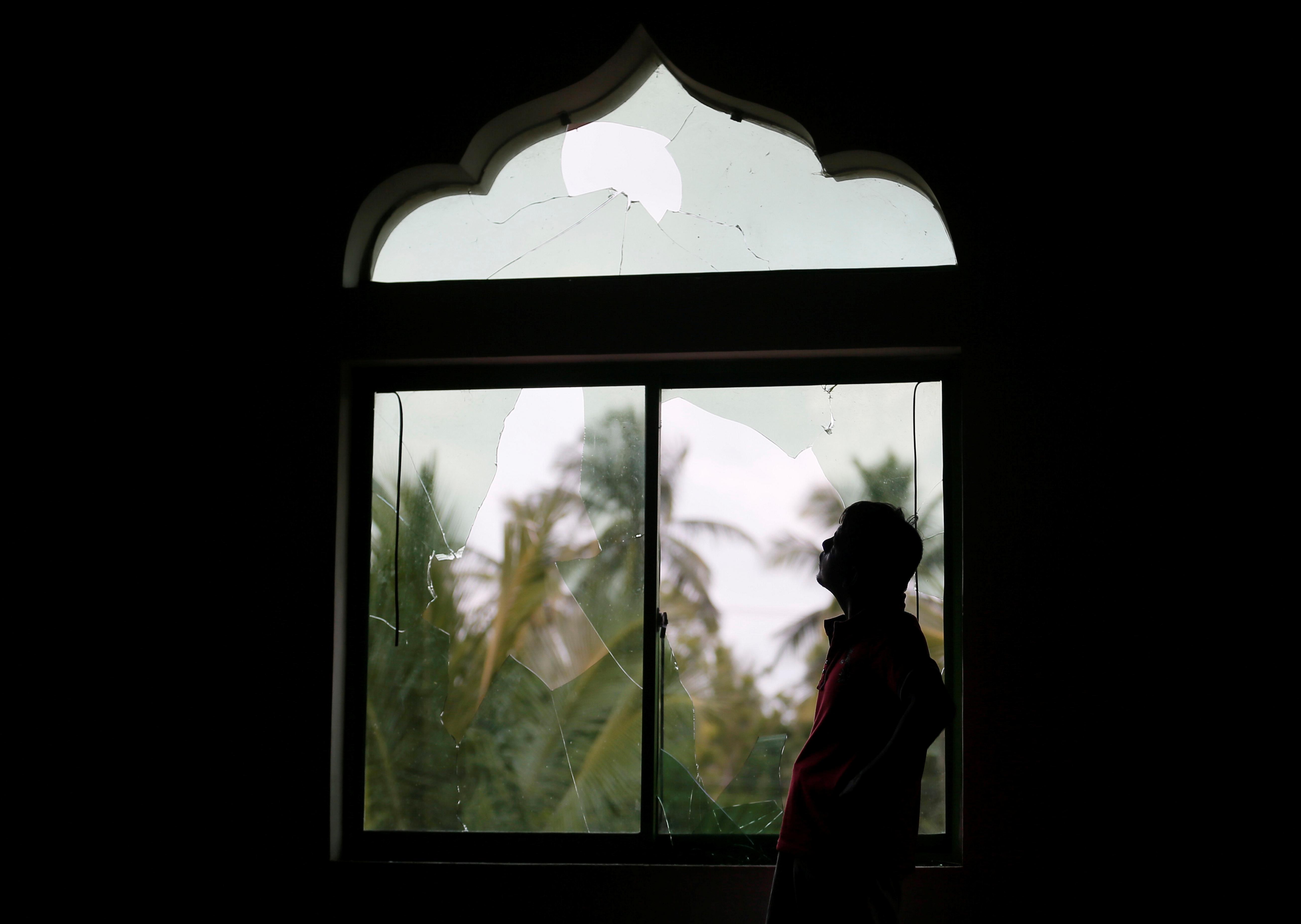 مواطن سريلانكى يقف أمام نافذة المسجد الذى هاجمه الغوغاء