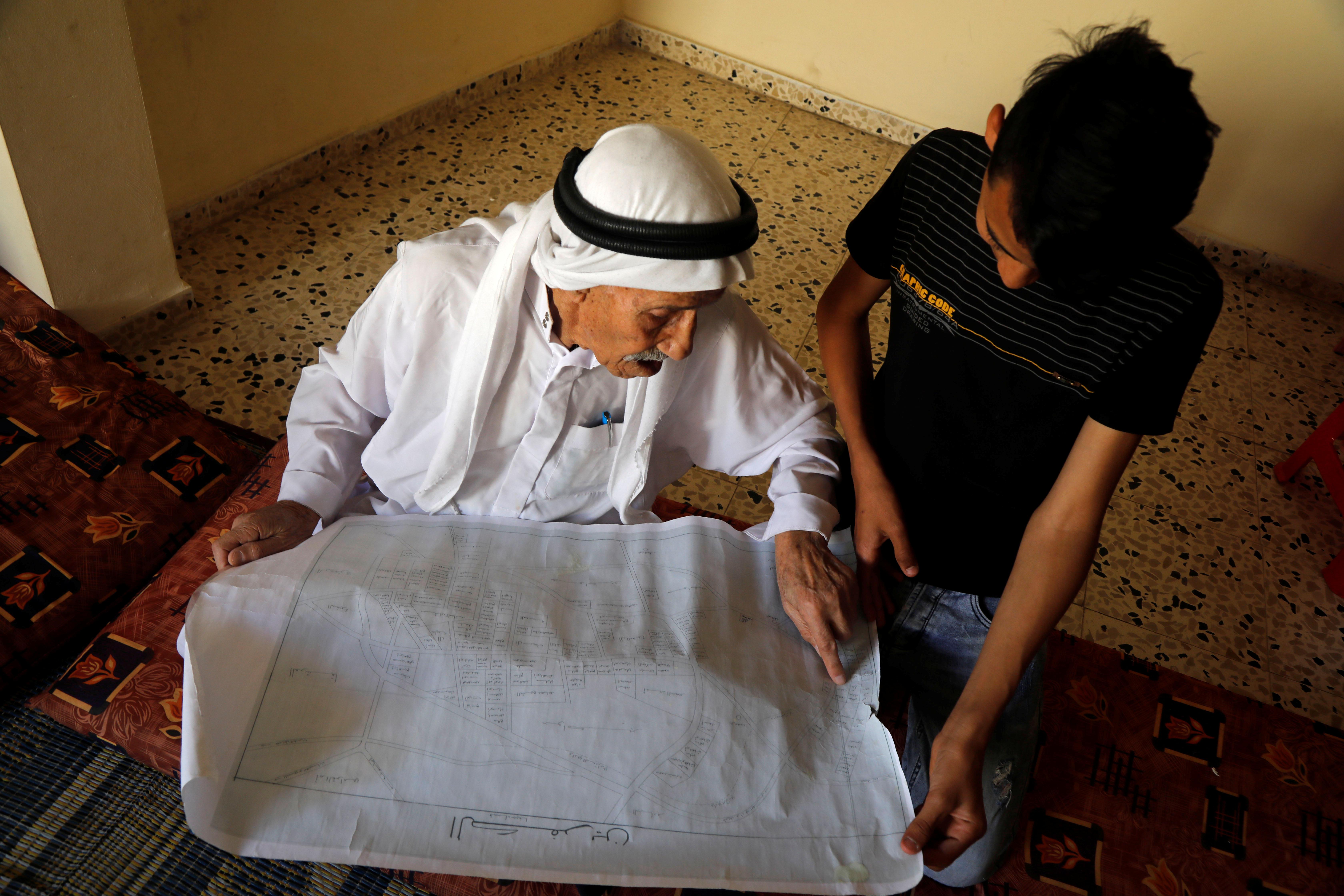 مسن فلسطينى يظهر خريطة لبلدته الفلسطينية