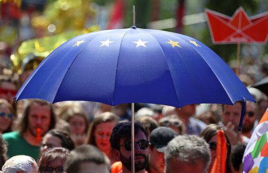 متظاهر يحمل مظلة بشعار الاتحاد الأوروبى