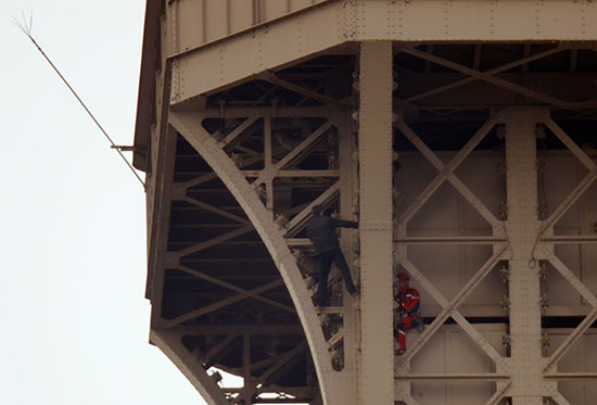 الشاب يبتعد عن رجل الإنقاذ اعلى برج إيفل