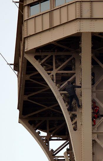 رجل إنقاذ يحاول الوصول إلى الشاب أعلى برج إيفل