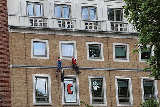 متظاهون يتدلون من أعلى مبنى شركة بى بى