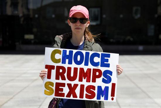 ناشطة-أمريكية-تحمل-لافتة-مناهضة-لترامب