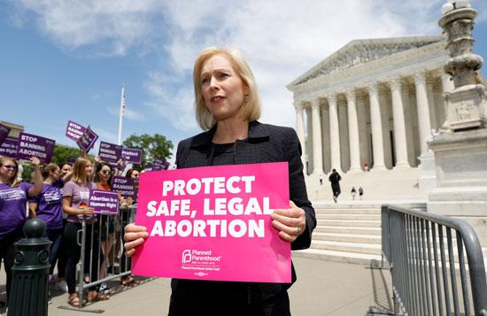 ناشطة-تحمل-لافتة-تدعو-لحماية-الإجهاض-الآمن-والقانونى