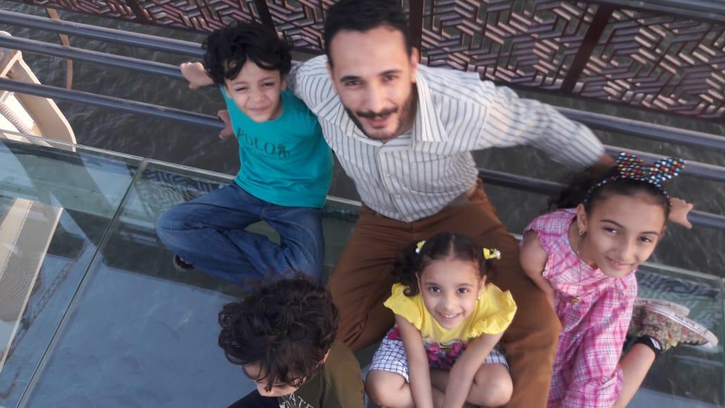 الأب مع أبنائه على الممشى الزجاجى