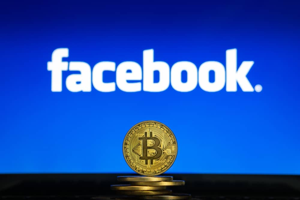 Bitcoin-on-a-stack-of-coins-with-Facebook-logo-on-a-laptop-screen.-Cryptocurrency-and-blockchain-adoption-getting-mainstream.-Slovenia-02-24-2019-Image
