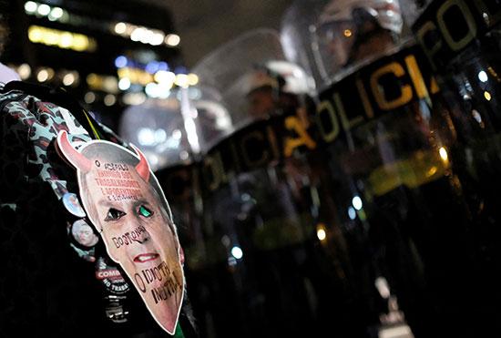 متظاهرة تحمل صورة ساخرة للرئيس على ظهرها