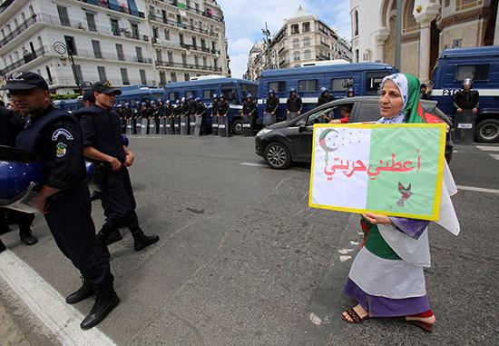 سيدة ترفع لافته خلال الاحتجاج