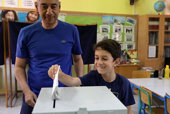 صفل يضع بطاقة الاقتراع الخاصة بأبيه فى صندوق الانتخابات