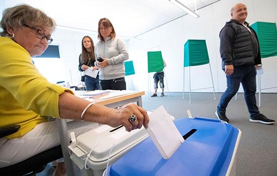 مسئولة بأحد اللجان تضع بطاقة اقتراع داخل الصندوق